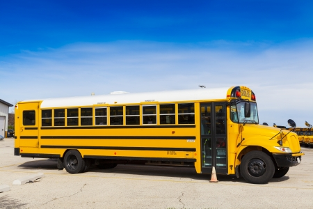 side view: Yellow School Bus With Blue Sky  Stock Photo