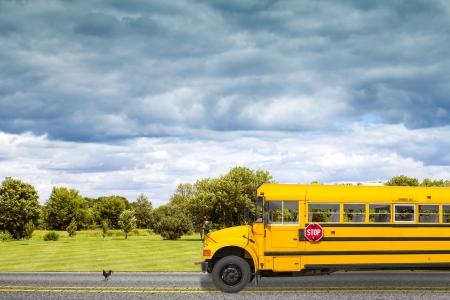午前中にアメリカの国道路上の学校のバス 写真素材