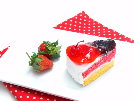 layer cake: rainbow layer cake and strawberry souce on white background