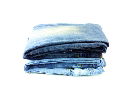 legs folded: stack of blue jeans on white background Stock Photo