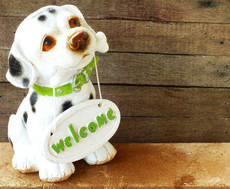 collectible: ceramic welcome dog on wooden background still life