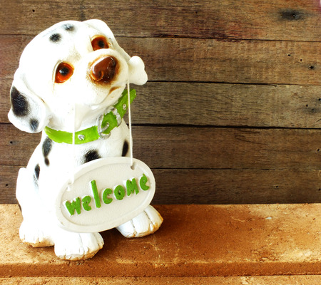 gnaw: ceramic welcome dog on wooden background still life