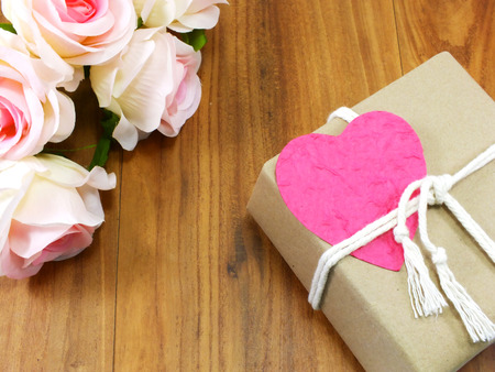 heart gift box: gift box wrapped in recycled paper with white rope and pink heart paper tag Stock Photo