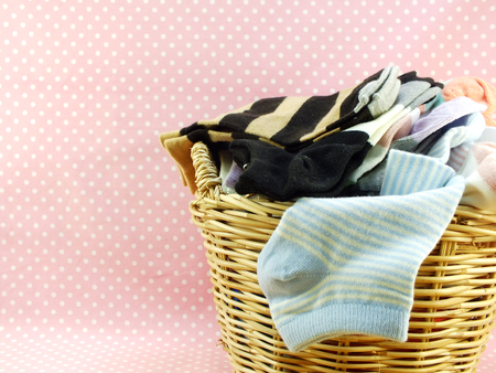 household tasks: multi colored socks and laundry basket Stock Photo