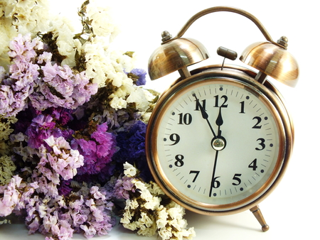 spring time with alarm clock and statice flowers bouquet background