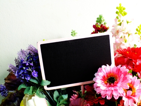 space background with bouquet of flowers and empty wooden tag