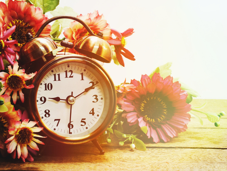 spring time with alarm clock and artificial flowers bouquet background