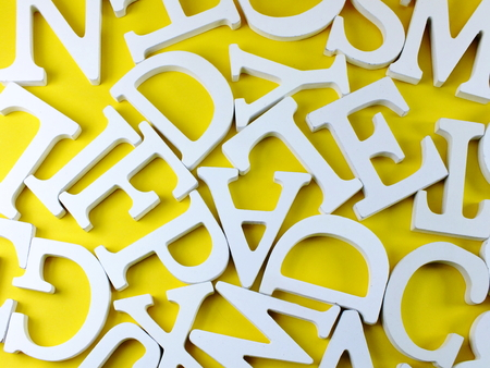 random white wooden alphabet letters top view on yellow background Stock Photo