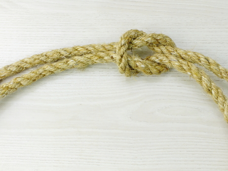 hemp rope knot isolated on wooden background