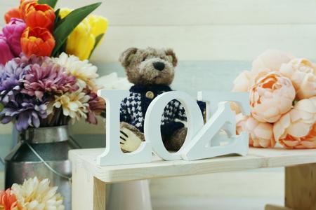love word wooden letter with artificial flowers decor Foto de archivo