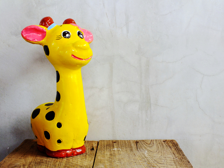cute giraffe statue ceramic with space copy on wooden background