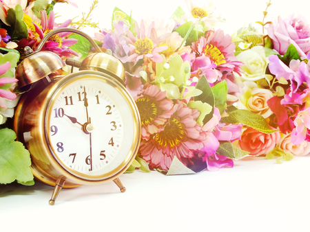alarm clock and artificial flowers bouquet with filter color