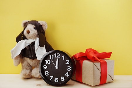 teddy bear and alarm clock with space copy on wooden background