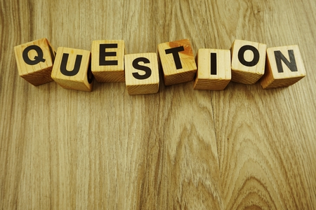 questions word in wooden cube alphabet letters top view on wooden background