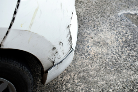close up of damaged scratching on the front of the white car Imagens