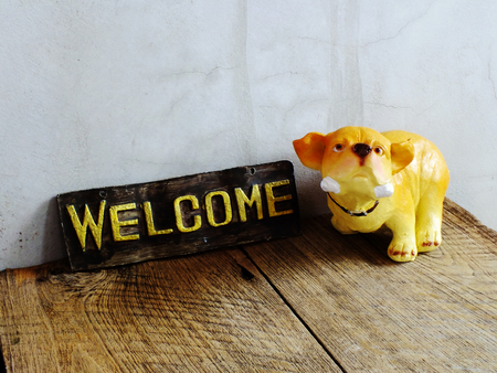 ceramic dog with welcome sign on wooden background
