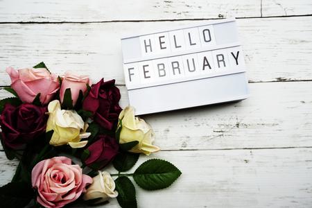 Hallo Februar Wort auf Leuchtkasten mit Rosenblumenstrauß auf Holzuntergrund Standard-Bild