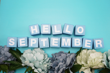 hello september alphabet letters with flower bouquet on blue background Zdjęcie Seryjne