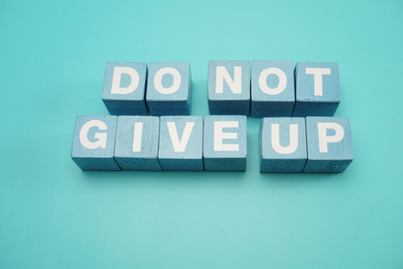 Do Not Give Up word made from wooden cubes with letters alphabet on blue background