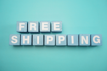 Free Shipping word created with cubes alphabet letters on blue background 版權商用圖片