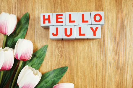 Hello July with tulip flower on wooden background