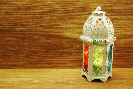 lighting with colorful on muslim lantern shining on wooden background