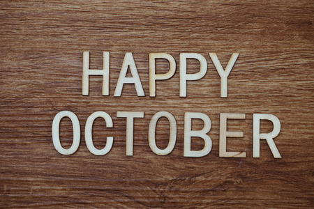 Happy October text message on wooden background