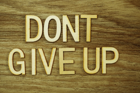 Don't Give Up text message on wooden background