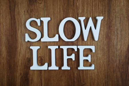 Slow Life alphabet letter with space copy on wooden background Stock Photo