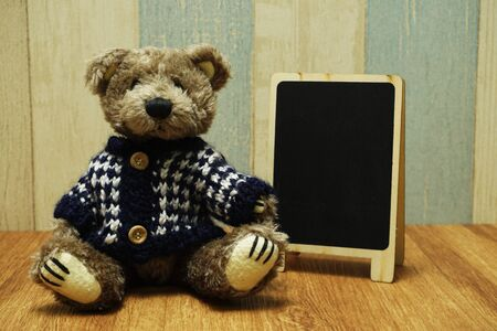 Teddy bear and blackboard easel wooden space background