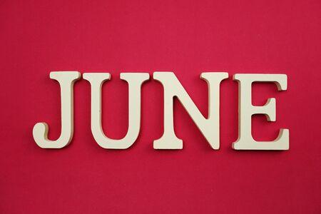 Juni-Alphabetbuchstabe mit Raumkopie auf rosa Hintergrund