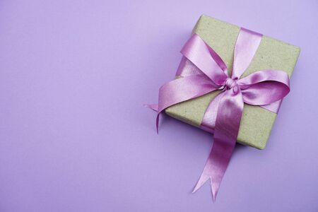 Gift box with pink bow ribbon on purple background Stock Photo