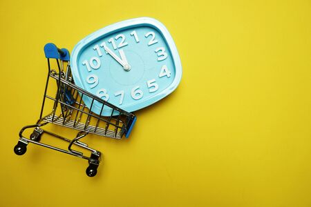 alarm clock and mini trolley cart with space copy on Yellow background