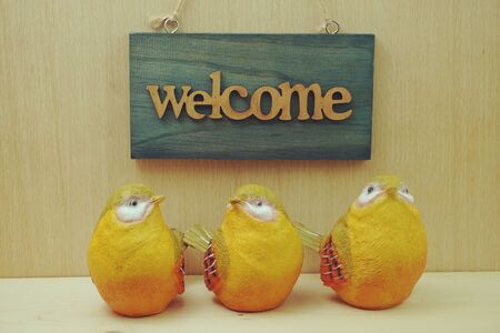 colorful bird statue and Welcome sign on wooden background