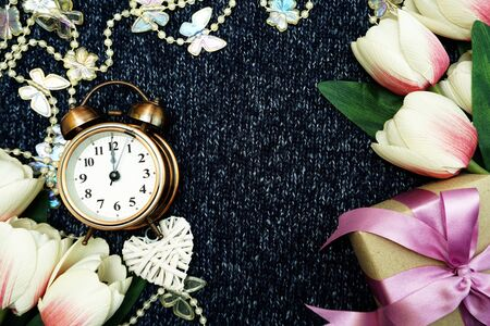 Vintage alarm clock with gift box and tulip flower with space copy Valentines day concept background