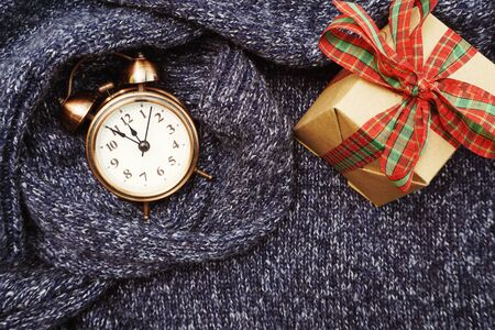 Winter background with alarm clock and gift box on blue knitted cloth texture background