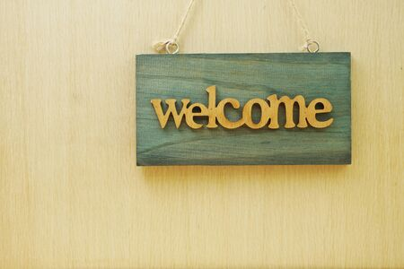 Wooden Welcome sign Hanging on space wooden background Banco de Imagens