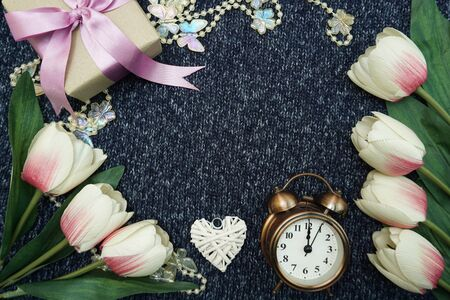 Vintage alarm clock with gift box and tulip flower with space copy Valentines concept background