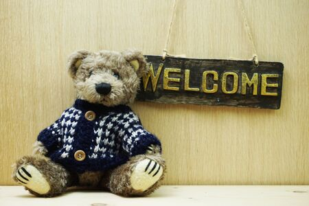 Welcome Sign and Teddy bear on wooden background