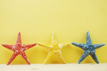 summer background with starfish figure and seashell decoration on yellow background Banco de Imagens