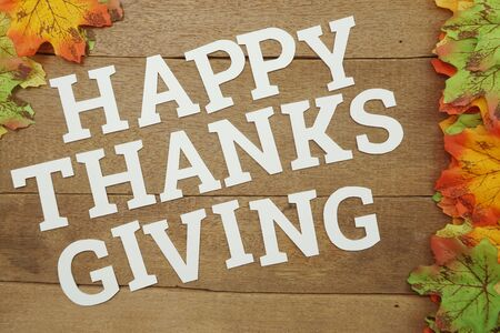 Happy Thanksgiving alphabet letters and maple leave on wooden background Banco de Imagens