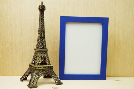 Space photo frame mock up with Eiffel tower souvenir on wooden background Banco de Imagens