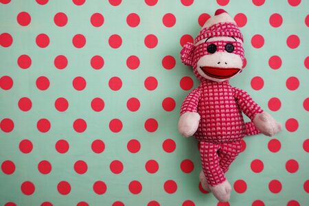 Pink Monkey Doll Top view on Pink and green Polka dot background Banco de Imagens