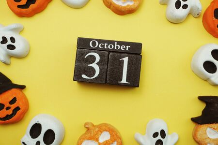 Halloween 31 October with skull and pumpkin decorate with space copy on yellow background