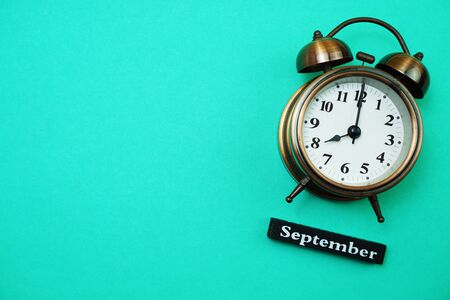 Alarm clock and September calendar with space copy on green mint background; 版權商用圖片