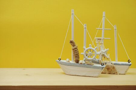 Nautical background with Sailboat Model on yellow background
