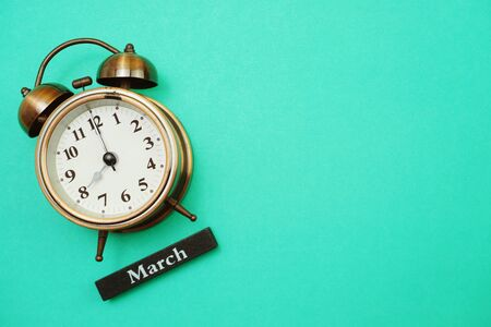 Alarm clock and March calendar with space copy on green mint background