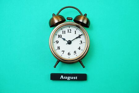 Alarm clock and August calendar with space copy on green mint background Banco de Imagens