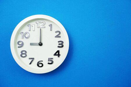 White round clock showing Nine oclock on blue background Banco de Imagens
