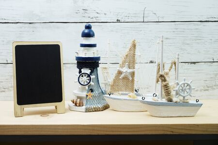 Nautical background with Sailboat Model with black board space copy on wooden background Фото со стока